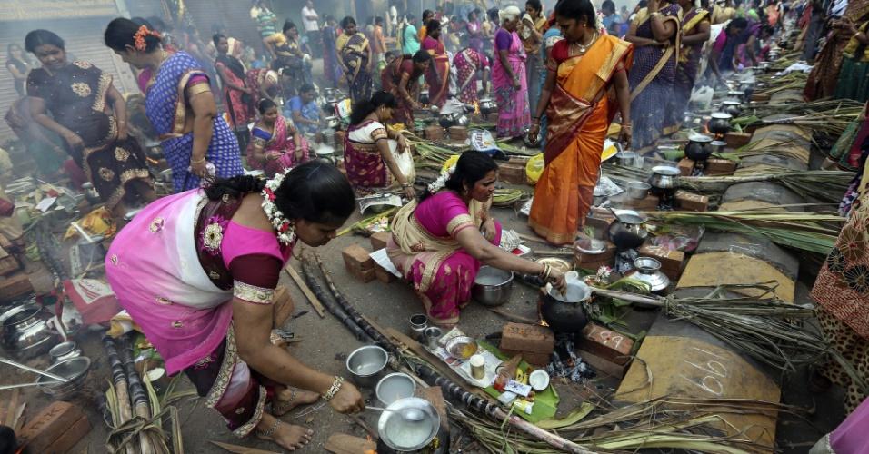 15.jan.2015 - Mulheres cozinham na rua durante celebração do festival Pongal em Mumbai, na Índia. O Pongal, que dá nome ao festival, é um prato de arroz cozido com leite, açúcar mascavo e outros doces. O oferecimento do prato busca agradecer ao sol e ao clima para conseguir uma colheita rica