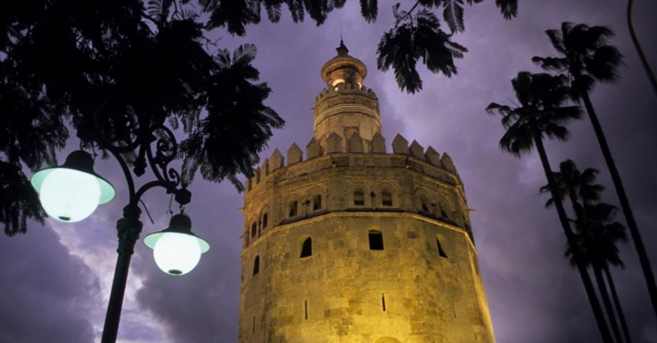 Farol na noite. O sol se põe atrás da Torre do Ouro, em Sevilha, na Espanha. A torre de observação militar tem este nome por conta das telhas douradas que a enfeitaram um dia