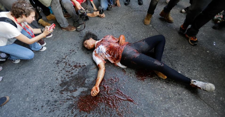 26.jan.2016 - Uma manifestante realiza um ato teatral em alusão à violência e repressão dos protestos contra o aumento da tarifa do transporte público em São Paulo