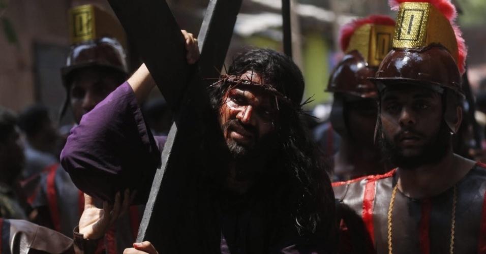 25.mar.2016 - Ator caracterizado como Jesus Cristo carrega cruz durante celebração da Sexta-feira Santa em Mumbai, na Índia
