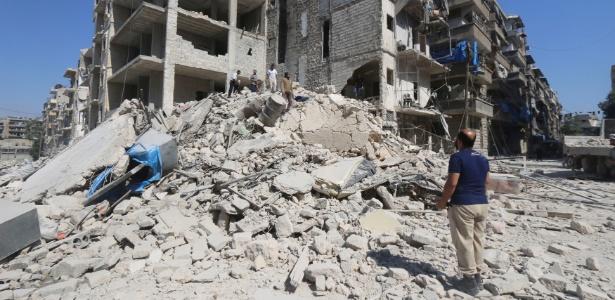 Homens buscam sobreviventes em escombros de edifícios danificados em ataques