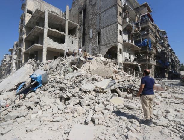 Homem procura por sobreviventes após ataques aéreos na cidade síria de Aleppo