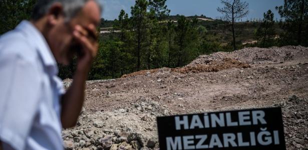 """Homem diante da placa """"Cemitério dos Traidores"""", escrito em turco e de covas sem identificação, em Istambul"""