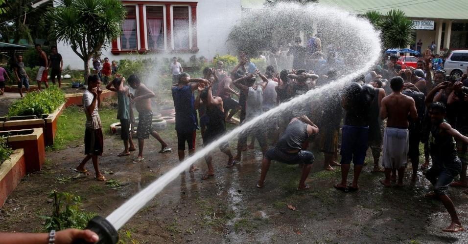 24.set.2016 - Funcionários lança jato d'água em direção a usuários de drogas que participam de programa de reabilitação em La Union, norte das Filipinas