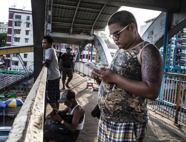 Homem usa smartphone na região central de Yangon, em Mianmar - MATHIEU WILLCOCKS/NYT