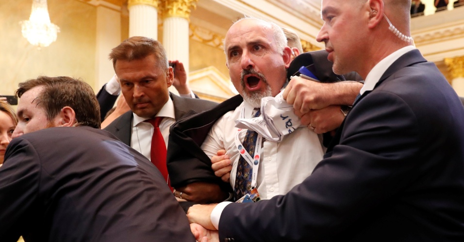 16.jul.2018 - Homem é expulso de entrevista coletiva para a imprensa com presidente dos EUA, Donald Trump, e da Rússia, Vladmir Putin; ele carregava papel que dizia Tratado de proibição nuclear, em inglês