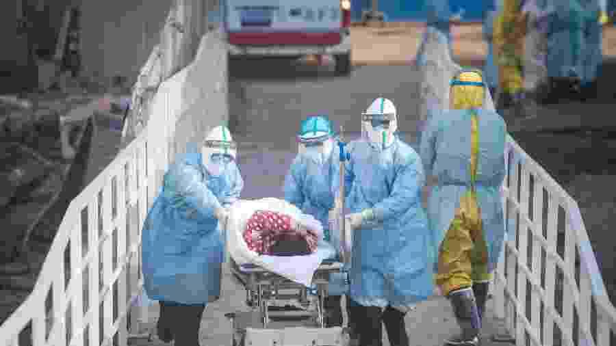 Médicos auxiliam primeiros pacientes infectados com o novo coronavírus na transferência para as enfermarias de isolamento no Hospital Huoshenshan, em Wuhan - Xinhua/Xiao Yijiu