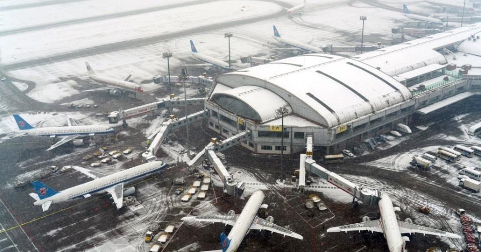 23.nov.2015 - Aviões ficam estacionados no Aeroporto Internacional de Pequim, na China, por causa de forte nevasca. As tempestades de neve que atingiram o país nos últimos dias interromperam o tráfego, atrasaram voos e várias viagens de trem-bala