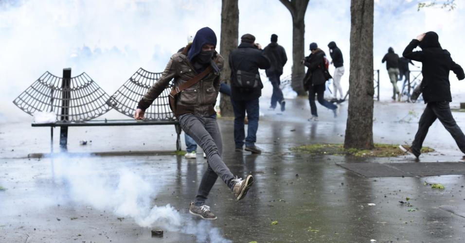 9.abr.2016 - Jovem chuta uma bomba de gás lacrimogêneo durante confronto entre policiais franceses e manifestantes que participavam de ato político. O protesto foi convocado em repúdio às reformas trabalhistas propostas pelo governo do presidente François Hollande