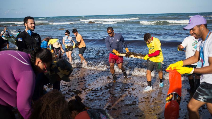 Militares do Exército, voluntários e funcionários ligados ao meio ambiente realizam limpeza e retirada de óleo na Praia de Itapuama, em Cabo de Santo Agostinho, na Região Metropolitana do Recife  - Tiago Queiroz/Estadão Conteúdo