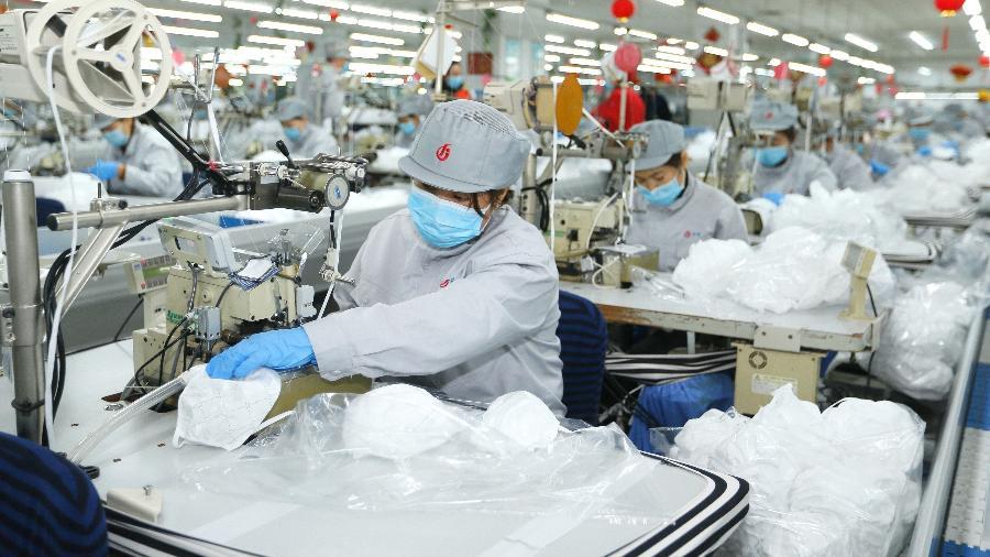 Trabalhadores produzem máscaras de proteção para o rosto em meio à quarentena pelo coronavírus na província de Qingdao, na China - Liang Xiaopeng/Xinhua
