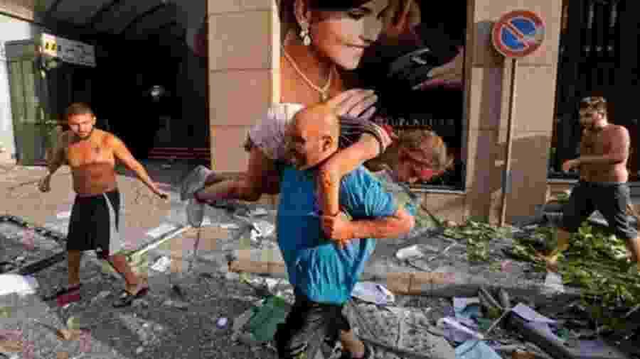 Homem retira mulher ferida de escombros em Beirute - Getty Images