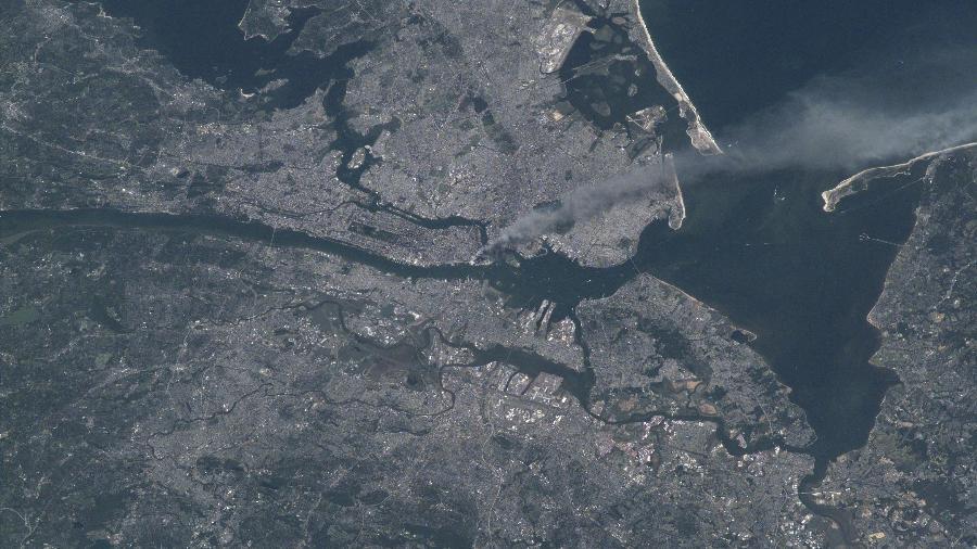 Nuvem de fumaça sobe da área de Manhattan depois que dois aviões colidiram com as torres do World Trade Center - Nasa