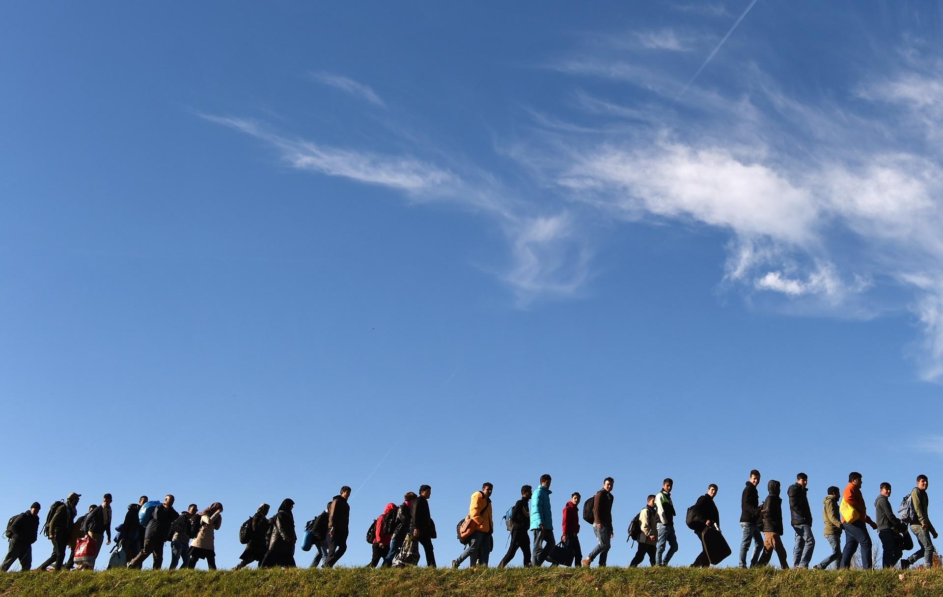 2.nov.2015 - Imigrantes caminham em direção ao primeiro posto de registro da Polícia Federal da Alemanha depois de cruzar a fronteira com a Áustria, no vilarejo de Simbach
