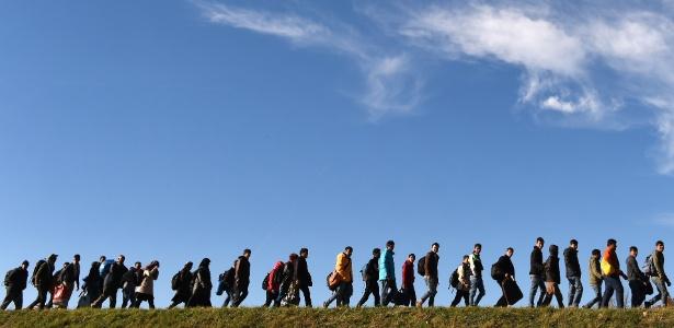 Imigrantes caminham em direção ao primeiro posto de registro da Polícia Federal da Alemanha depois de cruzar a fronteira com a Áustria, no vilarejo de Simbach