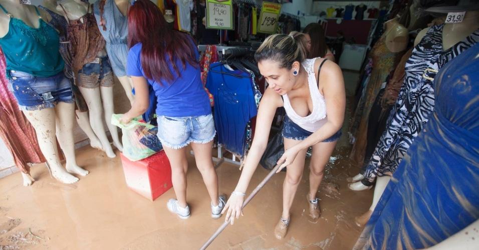 12.mar.2016 - Comerciantes e moradores das imediações da estação da CPTM de Franco da Rocha, na Grande São Paulo, começam a limpar lama que ficou após alagamento baixar. Uma pessoa morreu afogada neste sábado (12) ao tentar atravessar um ponto de alagamento na cidade