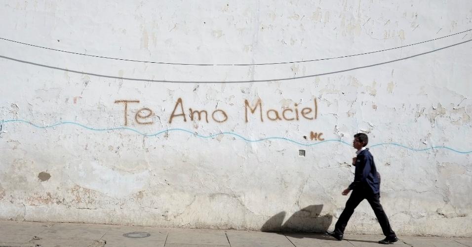 """18.jul.2016 - Jovem caminha por uma rua ao lado de um muro onde se lê """"Te amo Maciel"""", em Sucre, na Bolívia"""