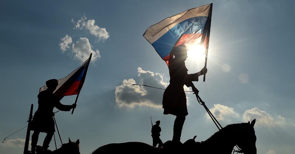 22.ago.2016 - Em cima de um cavalo, homens e mulheres carregam bandeiras da Rússia no Dia Nacional da Bandeira celebrado em Moscou. O país comemora o 25º aniversário da abortada tentativa de golpe contra o presidente soviético Mikhail Gorbachev, ocorrida em 1991. Na data, a bandeira russa foi hasteada na Casa Branca local em vez da soviética