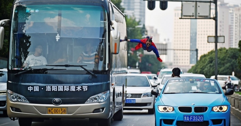 12.set.2016 - É o Super-Homem? Um artista parece voar enquanto se segura em um ônibus em movimento em Luoyang, na China. A performance faz parte de festival internacional de mágica na cidade