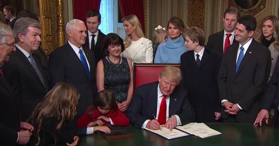 """20.jan.2017 - O presidente americano, Donald Trump, assina suas primeiras medidas no cargo, como a criação de um """"dia nacional do patriotismo"""""""