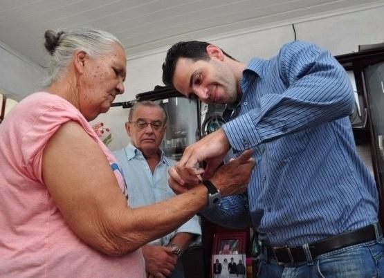 Idoso coloca pulseira de monitoramento que a franquia 24/7 Care usa para monitorar idosos a distância