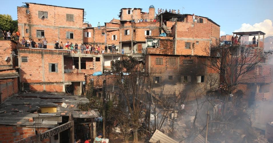 1.mar.2017 - Moradores observam o trabalho dos bombeiros para apagar um incêndio de grandes proporções que atingiu cerca de 50 barracos na favela de Paraisópolis, na zona sul de São Paulo