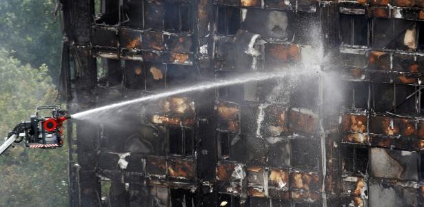 Equipe de bombeiros lança água em prédio destruído por incêndio em Londres