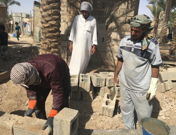 Sem ajuda para reconstrução, Sirhan Sallom, centro, reconstrói sua casa com suas economias a ajuda de seu filho em Karmah, no Iraque