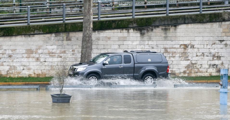 23.jan.2018 - Carro passa por rua alagada das margens do rio Sena, em Paris, França