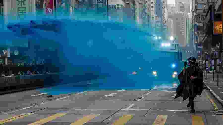 Manifestante corre à frente de um caminhão com canhão de água e tinta azul disparado pelas forças de segurança de Hong Kong - Dale de la Rey/AFP