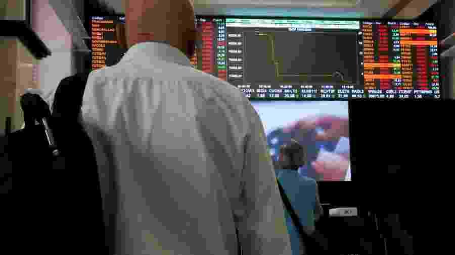 Pessoas observam painel na B3, a bolsa de valores de São Paulo, após circuit breaker - RAHEL PATRASSO