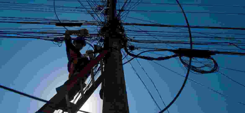Técnico de telecomunicação instalando cabos em poste na cidade de Osasco (SP) - Luiza Sigulem/Folhapress