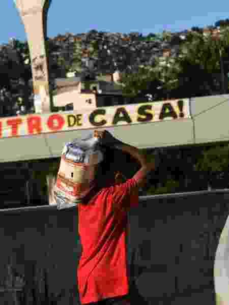 Um menino carrega doações entregues na favela da Rocinha durante a pandemia no Rio de Janeiro - RICARDO MORAES/REUTERS