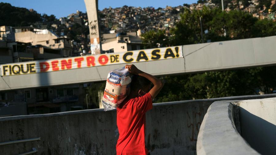 Um menino carrega doações de ajuda fora da favela da Rocinha durante pandemia - RICARDO MORAES/REUTERS