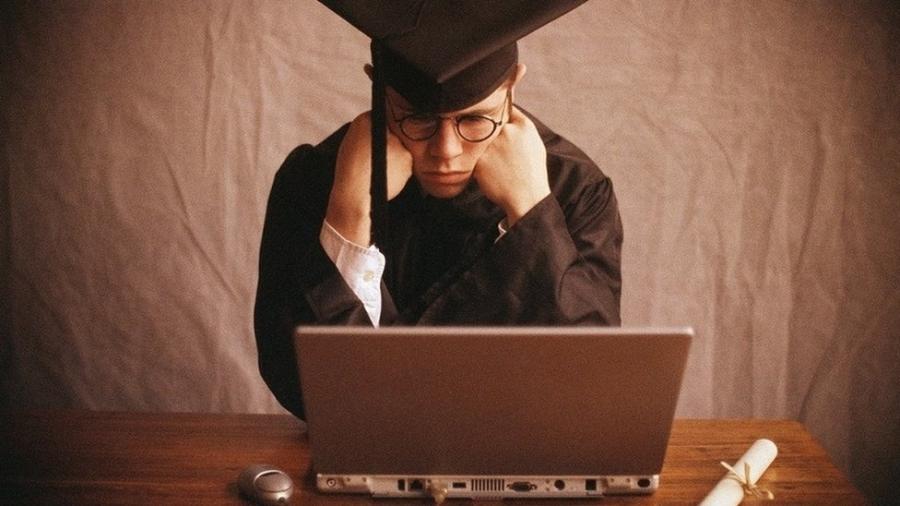 Jovem com beca e chapéu de formatura olha para um notebook com ar frustrado - Getty Images