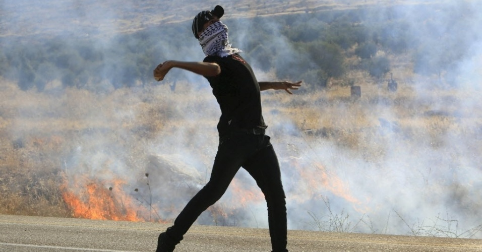 8.ago.2015 - Manifestante atira pedra na polícia israelense durante protesto após o funeral de Saed Dawabsheh, que morreu junto com seu bebê em um ataque de judeus extremistas no último dia 31. O enterro de Dawabsheh, neste sábado (8), reuniu centenas de pessoas na aldeia de Duma