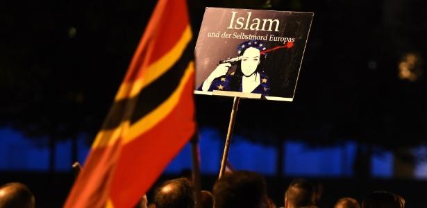 """5.out.2015 - Manifestante exibe cartaz com a frase """"Islã e o suicídio da Europa"""" durante protesto em Dresden, Alemanha, contra a entrada de refugiados no país. O protesto reuniu quase dez mil pessoas e foi convocado pelo movimento Pegida (Patriotas Europeus contra a Islamização do Ocidente, em alemão) - Tobias Schwarz/AFP"""