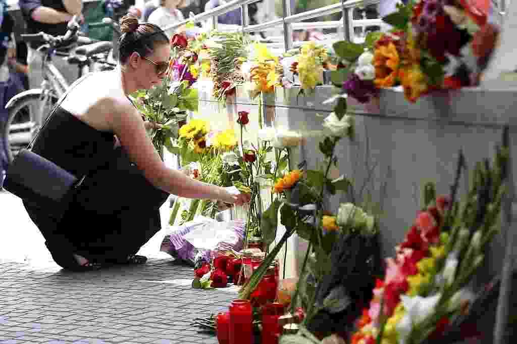 23.jul.2016 - Mulher coloca flores perto de shopping onde foi registrado um ataque na sexta-feira (22), em Munique, na Alemanha, que deixou dez mortos, entre eles o atirador que se matou - Arnd Wiegmann/Reuters