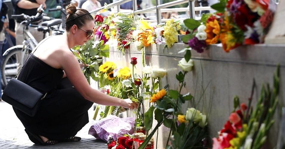 23.jul.2016 - Mulher coloca flores perto de shopping onde foi registrado um ataque na sexta-feira (22), em Munique, na Alemanha, que deixou dez mortos, entre eles o atirador que se matou
