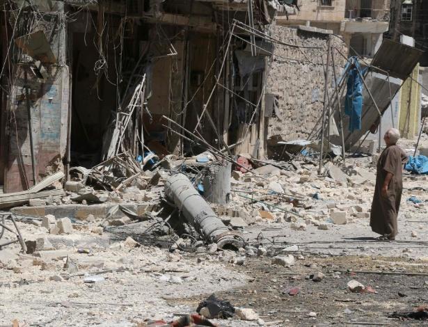 Residente do bairro de Tariq al-Bab, em Aleppo, verifica estragos causados por ataques aéreos na cidade síria