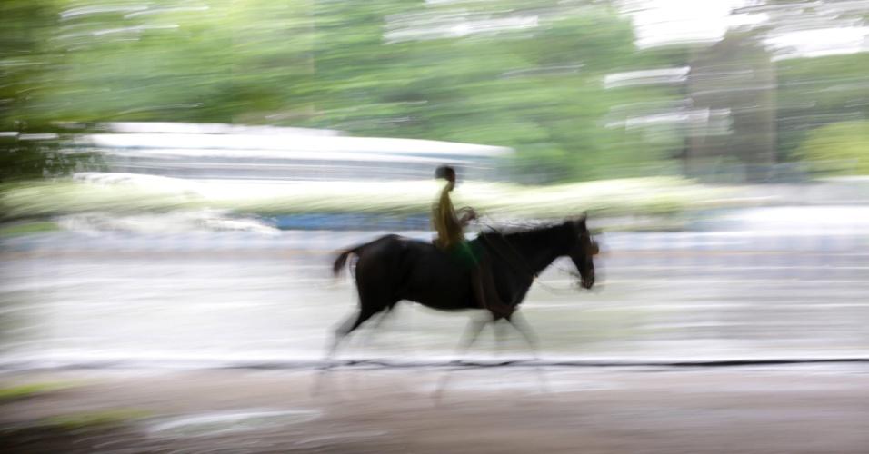 27.set.2016 - Fotografia com velocidade lenta de criança que monta a cavalo perto do Memorial Victoria em Calcutá, na Índia