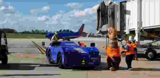 Um funcionário da companhia aérea se fantasiou de dinossauro para orientar um avião no aeroporto - Reprodução/Facebook Orlando International Airport (MCO)