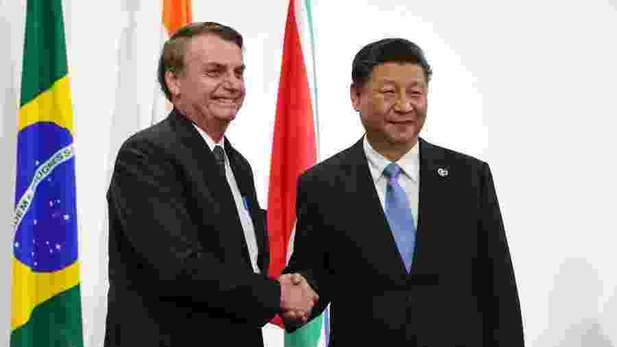 28.jun.2019 - Presidente Jair Bolsonaro e presidente da China,  Xi Jinping, durante encontro do G20, em Osaka, no Japão - Mikhail KLIMENTYEV / AFP