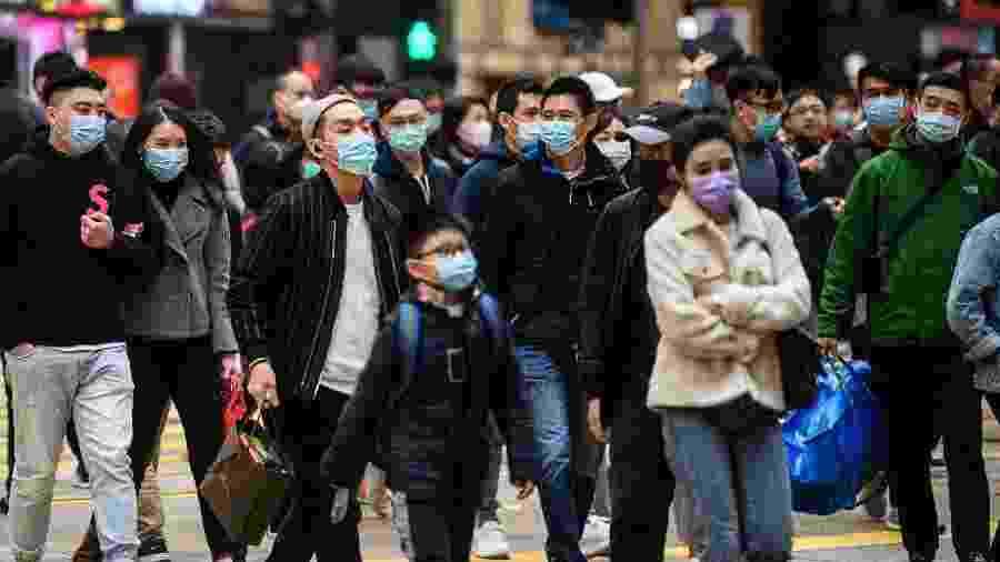 27.jan.2020 - Pedestres circulam por rua de Honk Kong enquanto o governo aumenta o fechamento de locais públicos em prevenção contra o novo coronavírus - Anthony WALLACE / AFP