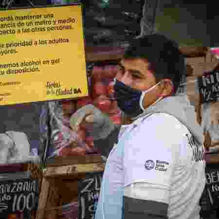 De máscara, feirante organiza sua barraca e olha o movimento em Buenos Aires, na Argentina - Marcelo Endelli/Getty Images