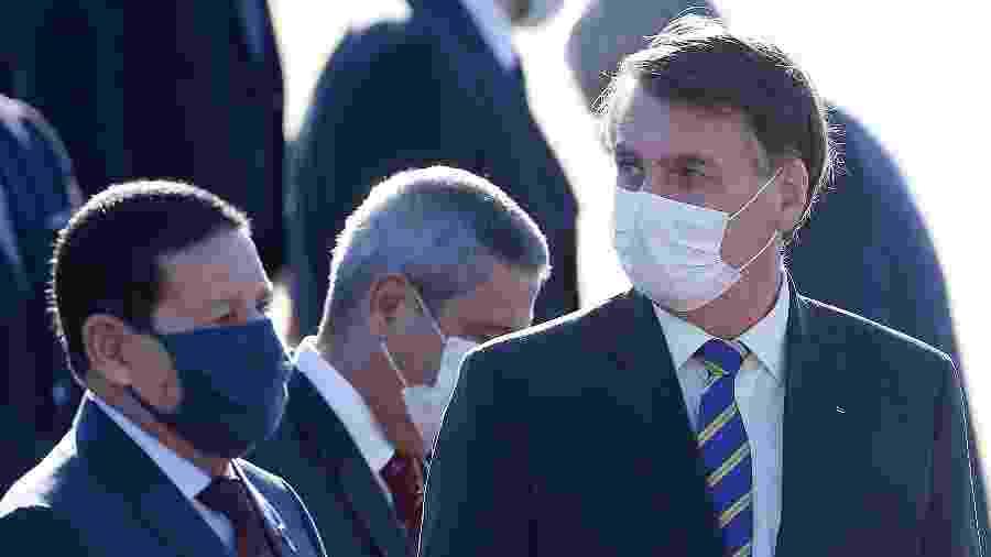 12.mai.2020 - O vice-presidente Hamilton Mourão e o presidente Jair Bolsonaro durante cerimônia de hasteamento da bandeira nacional, no Palácio da Alvorada - Dida Sampaio/Estadão Conteúdo