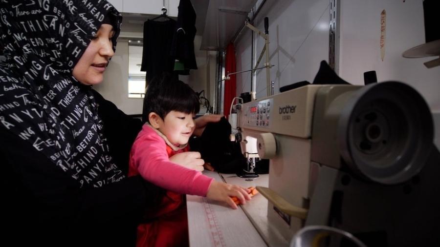 Kalbinur, fotografada com seu filho Merziye, costura roupas para sustentar sua família - BBC