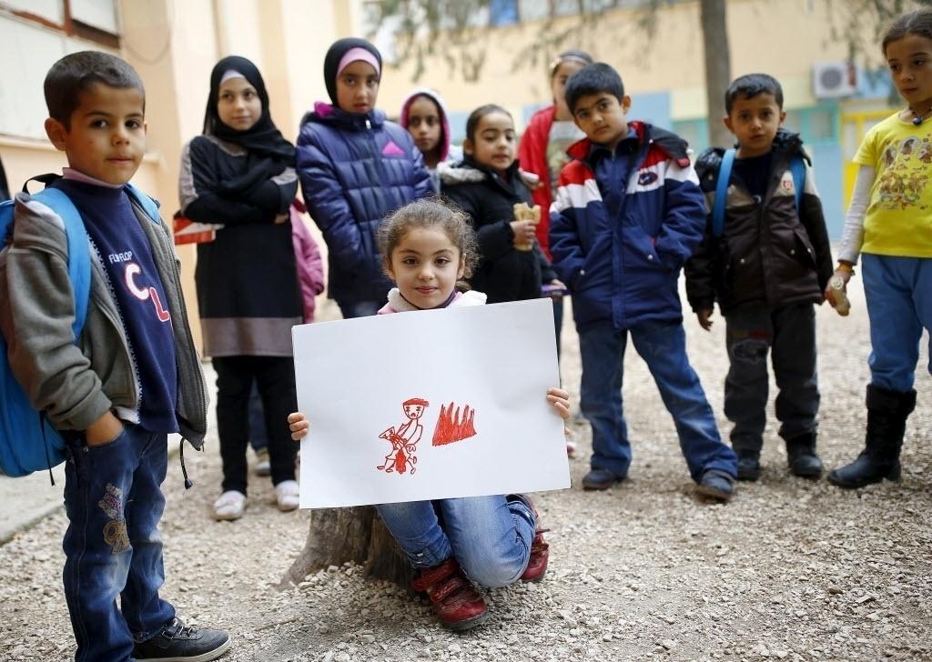 A garotinha síria Tesnim Faydo, 8, mostra ao lado de outras crianças seu desenho de uma mãe chorando pela filha ferida. Todos eles vivem no campo de refugiados de Yayladagi, na província de Hatay, perto da fronteira turco-síria, na Turquia. A guerra civil na Síria, que já deixou centenas de milhares de mortos, empurra outros tantos para o exílio, entre muitos deles crianças. Os desenhos das crianças do acampamento mostram memórias de suas casas, traumas vividos e esperanças para o seu futuro. Dos 2,3 milhões de refugiados sírios que vivem na Turquia, mais da metade são crianças