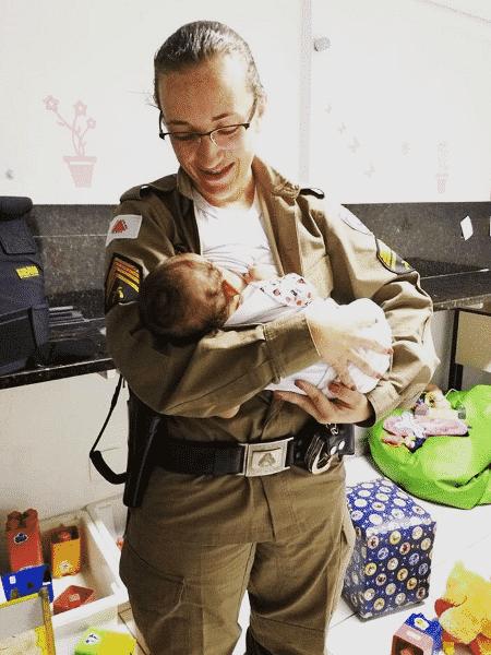 A sargento Marcilaine Rodrigues da Silva do Carmo amamenta a filha de uma vítima de violência doméstica atendida em delegacia de mulheres em Belo Horizonte - Divulgação/Polícia Militar
