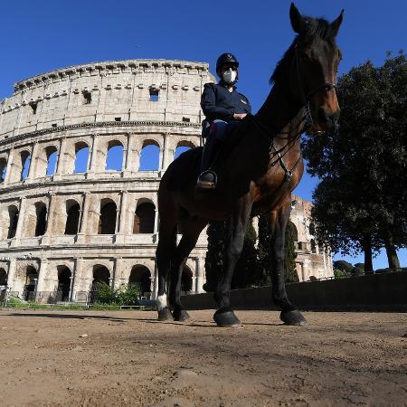 26.abr.2020 - Policial usa máscara em frente ao Coliseu, em Roma, Itália - Alberto Lingria/Reuters